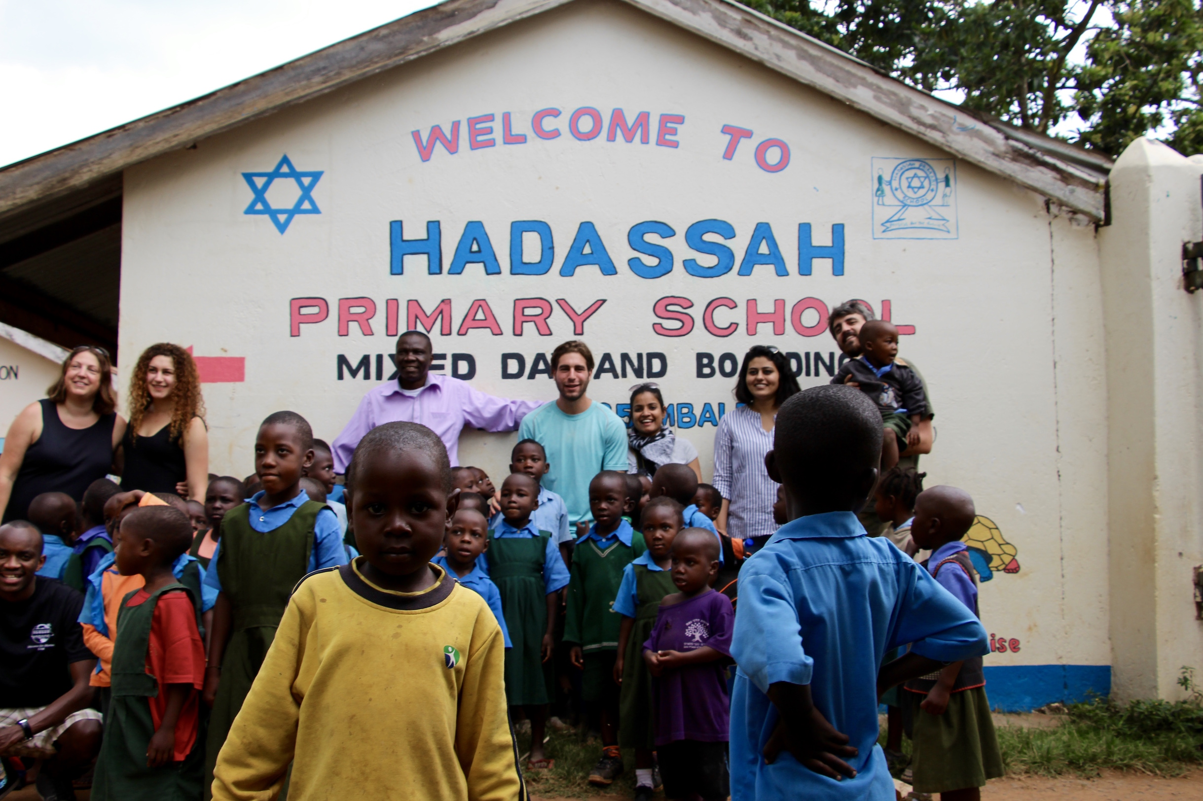 Photo (from left to right) of Ally, Lainie, Eli, Aaron Kintu Moses (Headmaster of Hadassa Elementary School), Aaron, Ruchi, Sukriti, and Leonard.