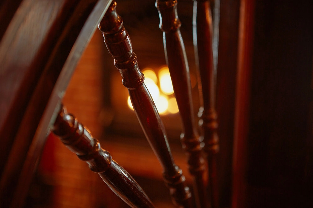 Surrounded by warm mahogany and the glow of the fireplace