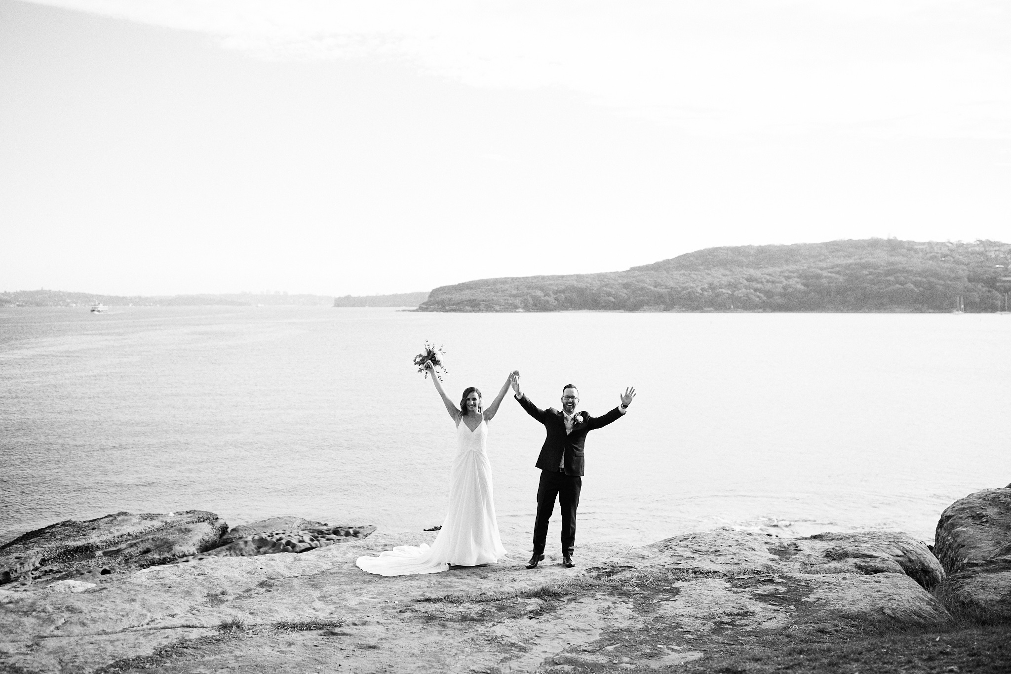 bride and groom celebrating on cliff top at manly pavilion by wedding photographer Joshua Witheford