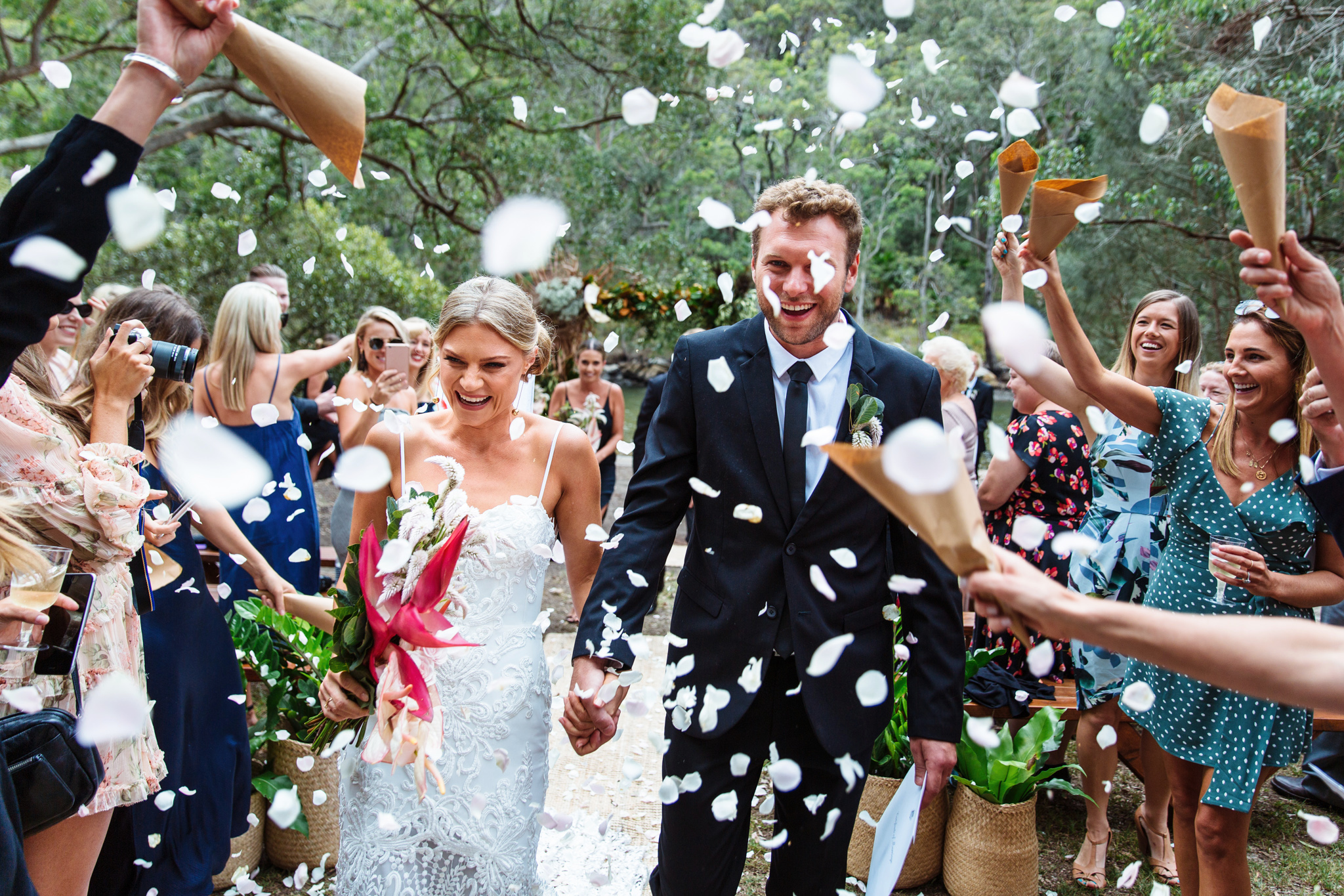 Bride and groom walking down the aisle while guests throw confetti in Narrabeen by Blue Mountains wedding photographer Joshua Witheford