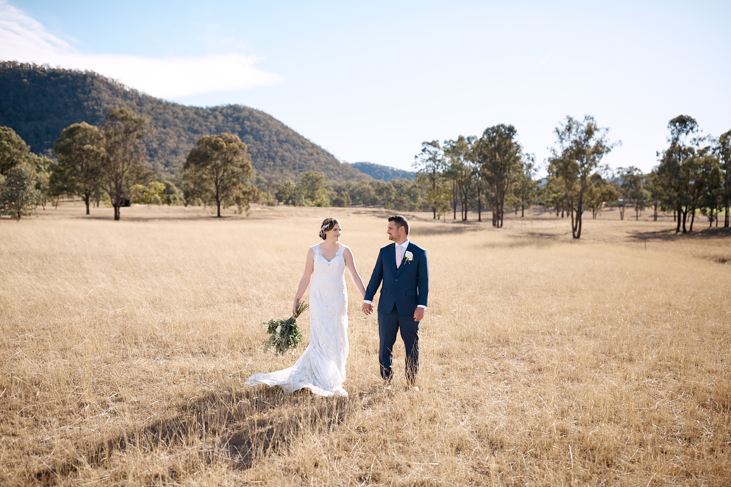 Bride and groom holding hands in field at Adams Peak in Hunter Valley by Blue Mountains wedding photographer Joshua Witheford