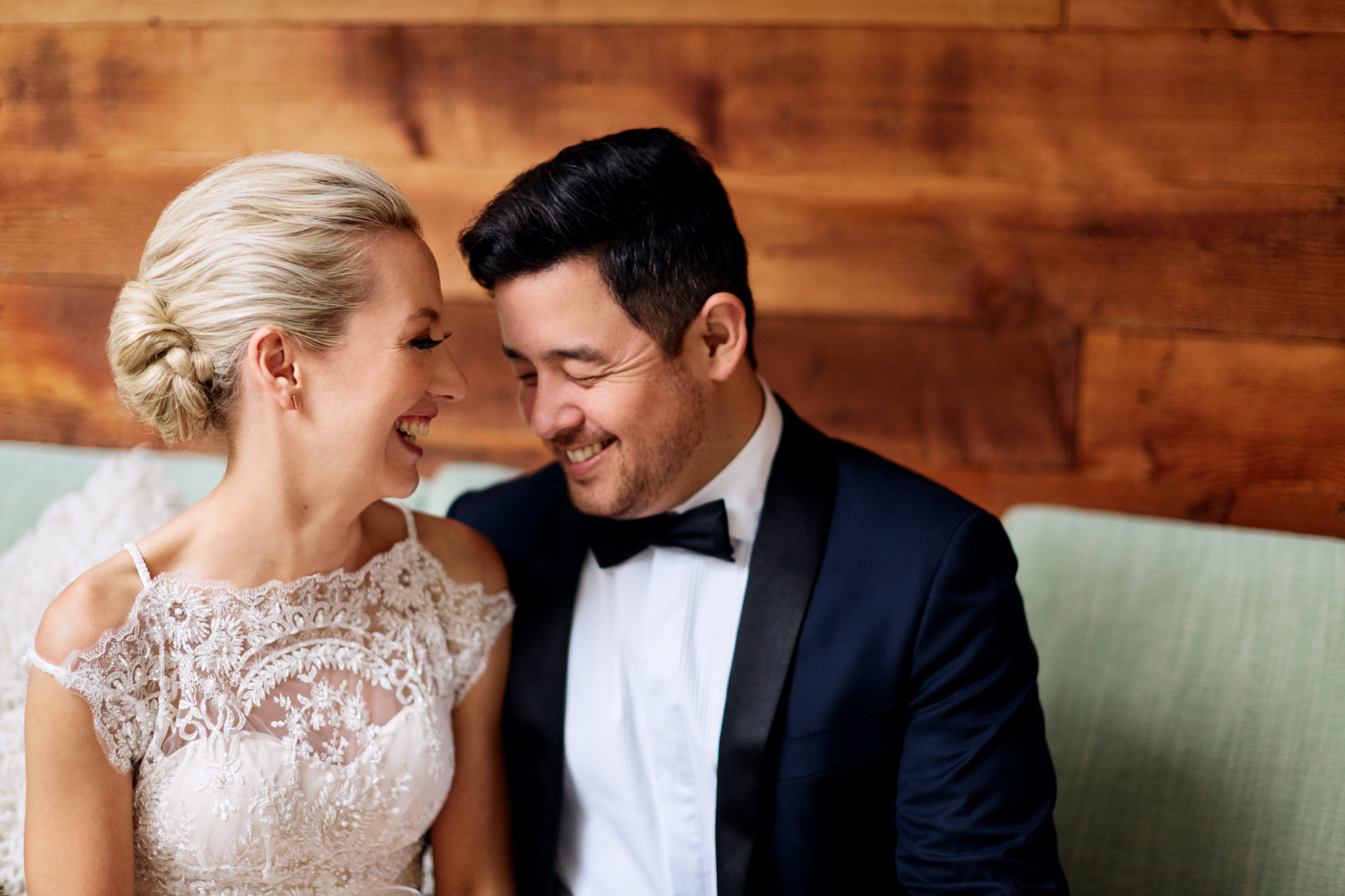 Bride and groom sitting indoors out of the rain laughing in Royal Botanic Gardens Sydney by Blue Mountains wedding photographer Joshua Witheford