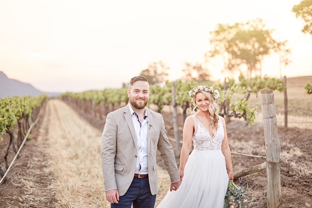 Bride and groom holding hands in vineyard at Estate Tuscany Hunter Valley by Blue Mountains wedding photographer Joshua Witheford