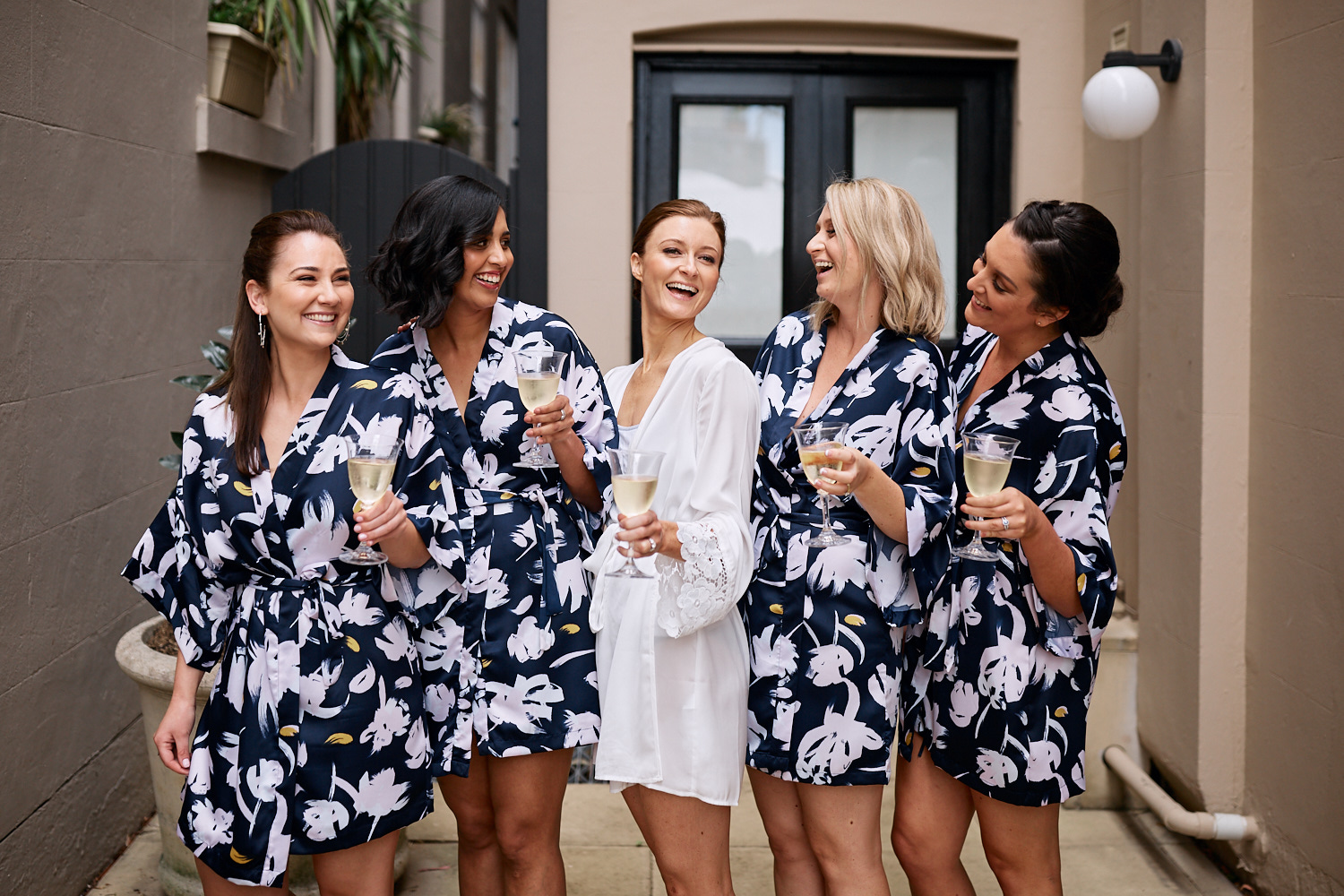 Bridesmaids wearing robes and holding champagne laughing