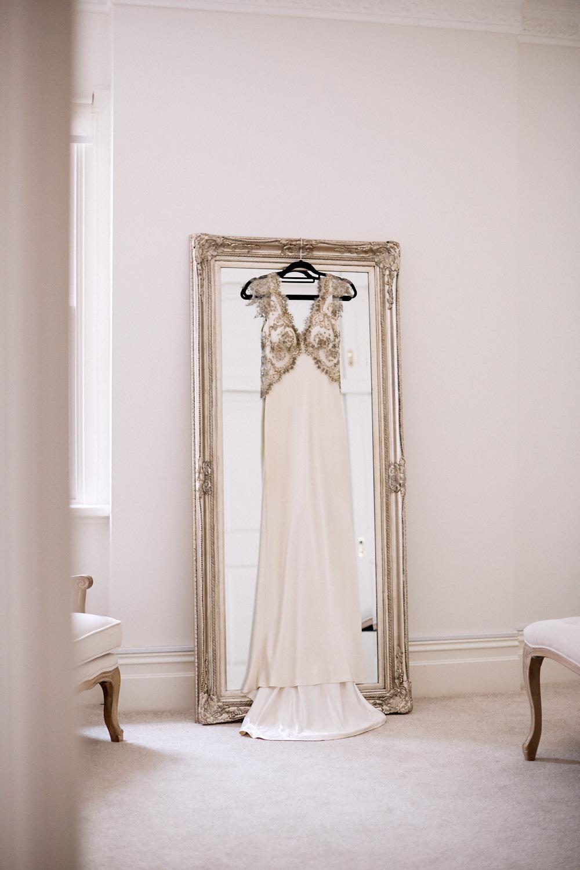 Adam Dixon wedding dress hanging on ornate mirror