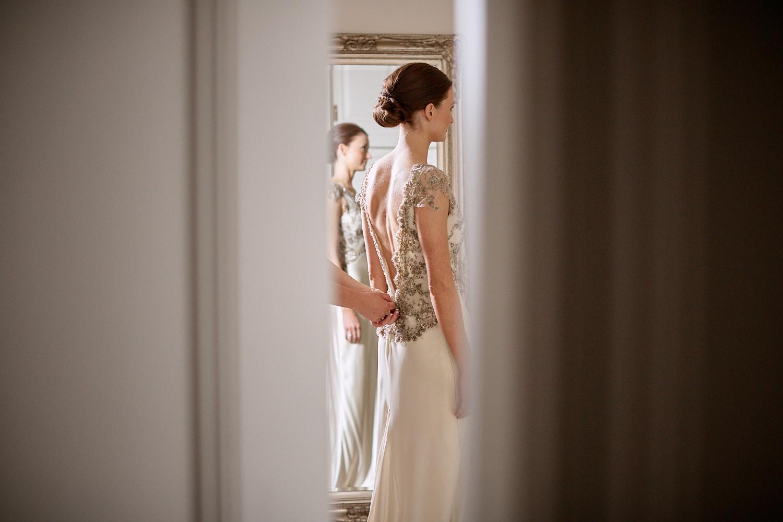 Bride dress being done up as seen through open door