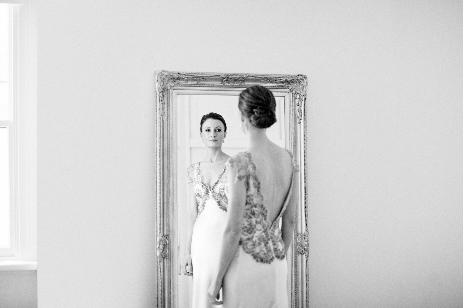 Black and white of bride wearing wedding dress in front of mirror