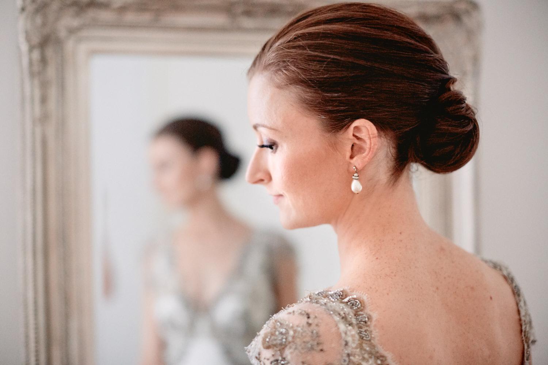 Bride standing in front of mirror wearing earrings.