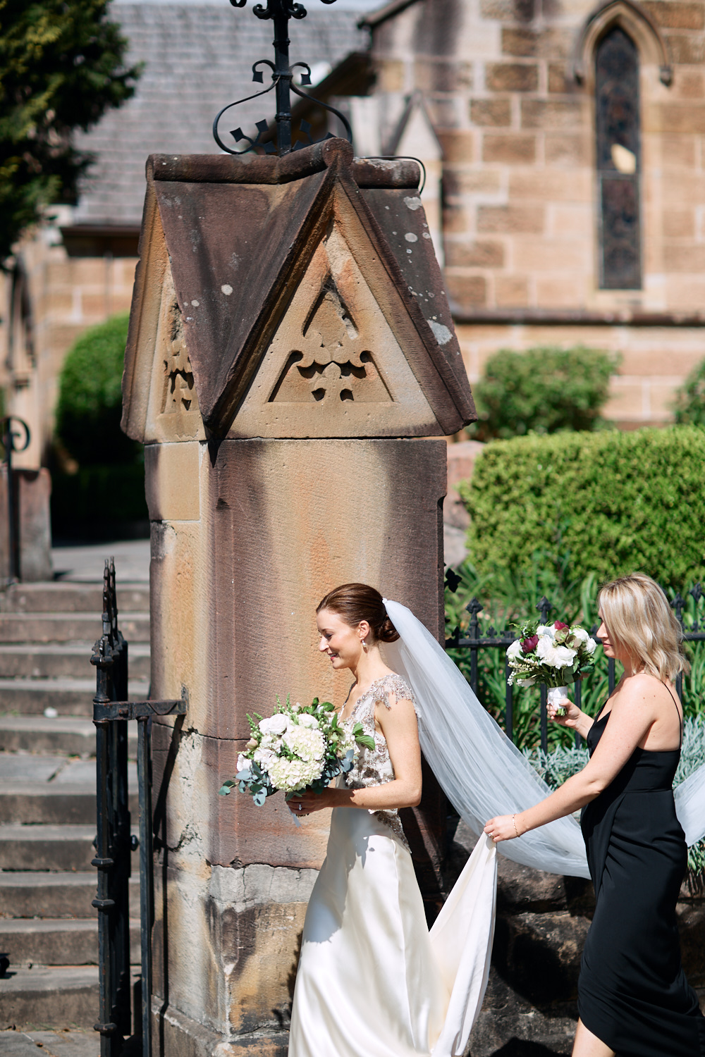 Maid of honour lifting brides dress in front of St Marks Anglican Church, Darling Point