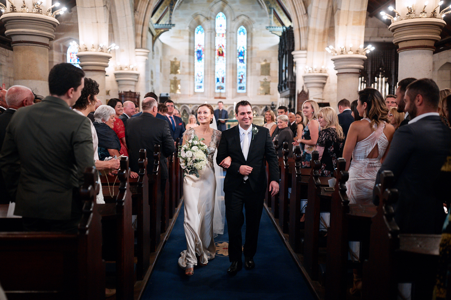 Newlyweds walking down aisle arm in arm with guests watching at St Marks Anglican Church, Darling Point
