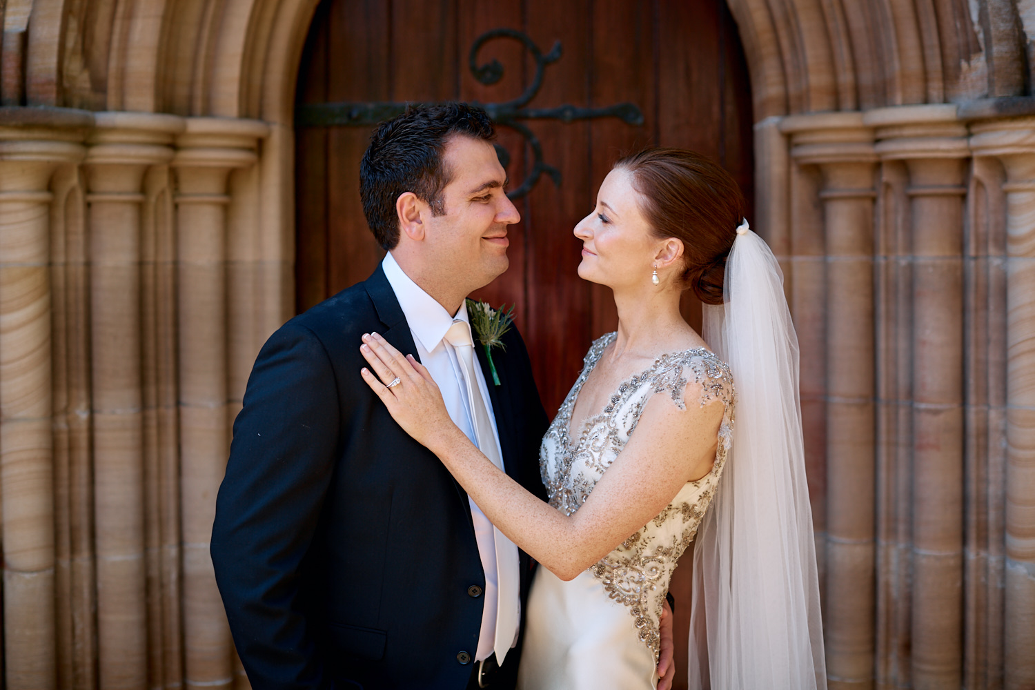 Portrait of bride and groom looking at each other in front of wooden door at St Marks Anglican Church, Darling Point