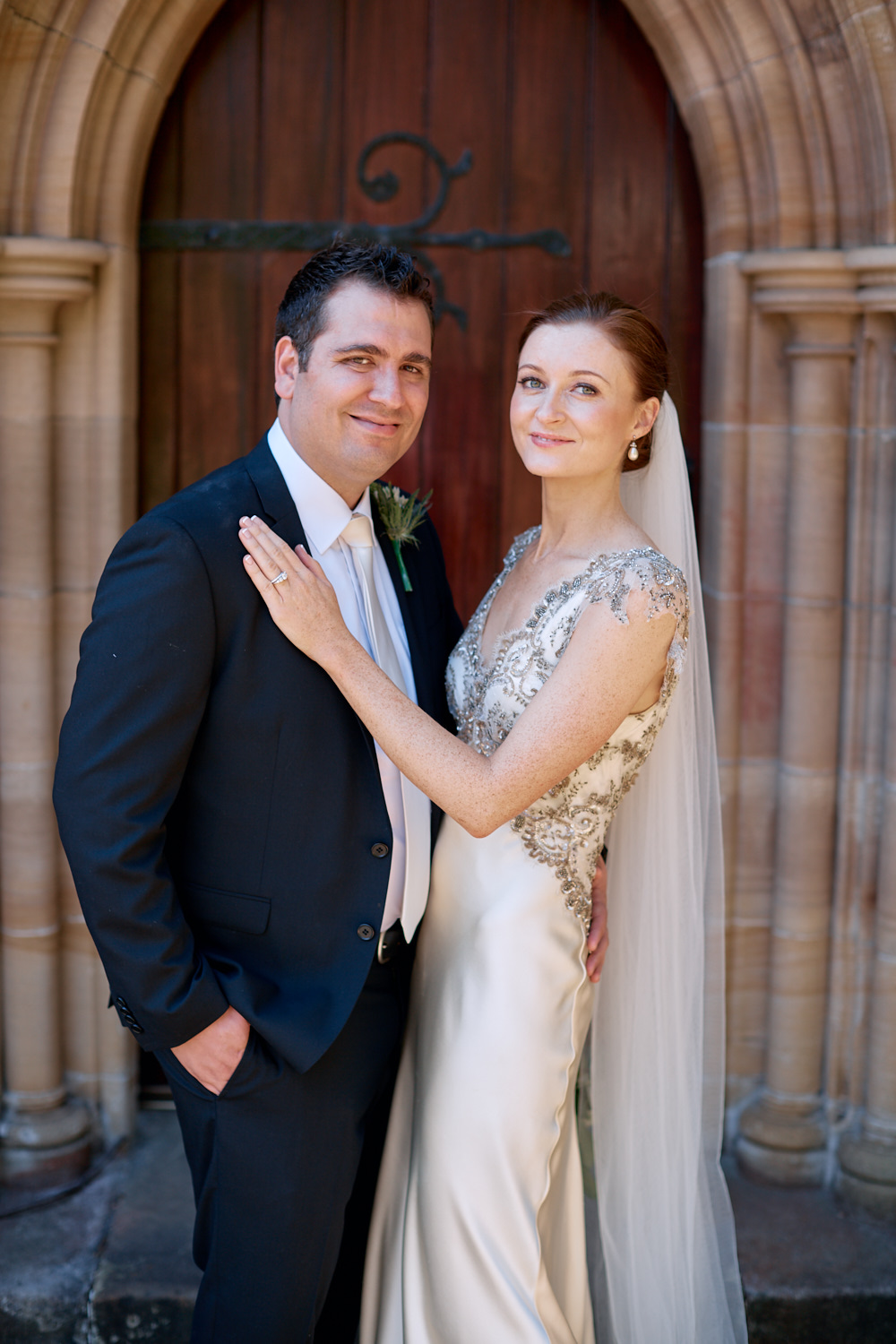Portrait of bride and groom in front of wooden door at St Marks Anglican Church, Darling Point