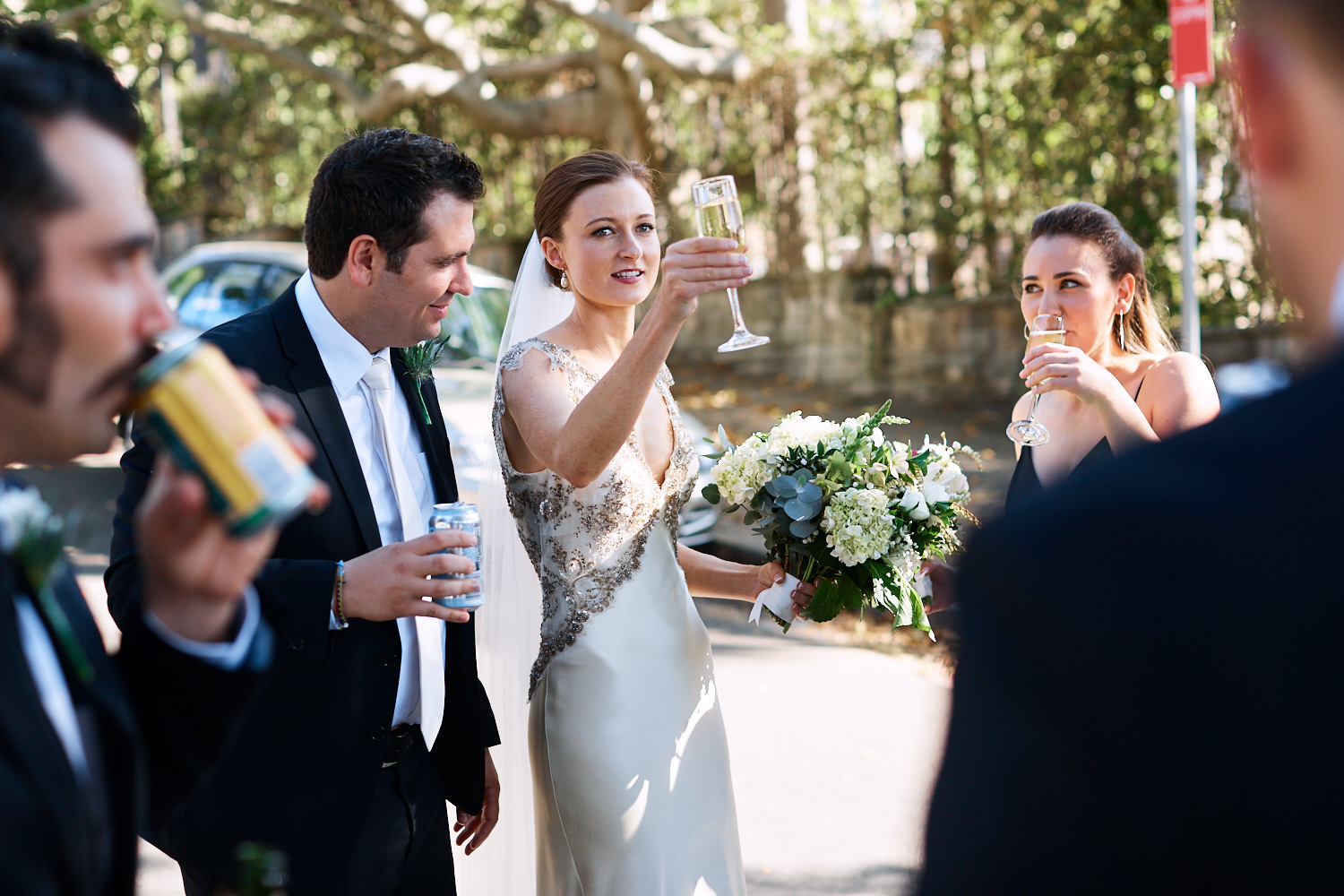 Bride raising a glass of champagne to bridal party
