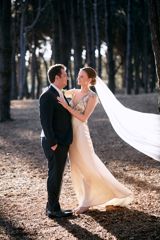 Bride holding groom with sunlight through veil in Pine Grove Woodlands Centennial Park Sydney
