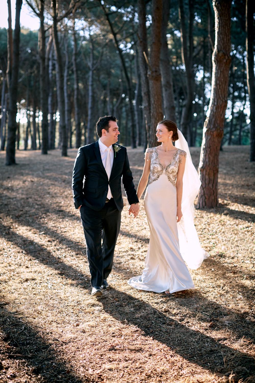 Bride and groom holding hands walking through n Pine Grove Woodlands Centennial Park Sydney