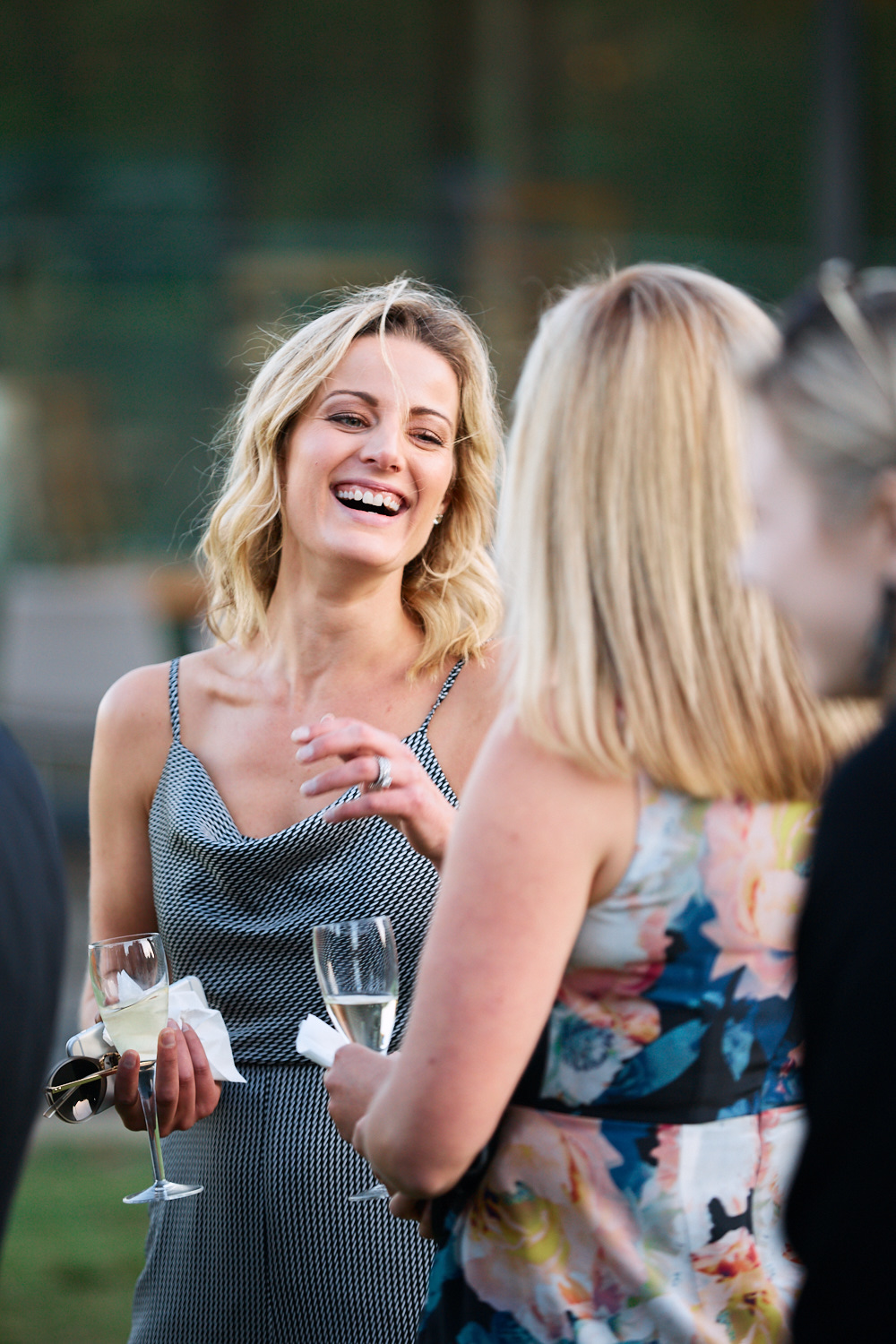 Woman holding champagne and laughing with guest at Centennial Homestead wedding