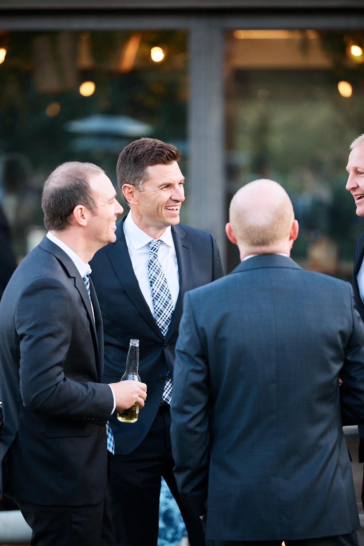 Men in suits talking at Centennial Homestead wedding