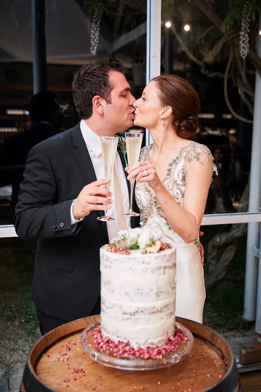 Newlyweds kissing while holding champagne flutes in front of wedding cake at Centennial Homestead wedding