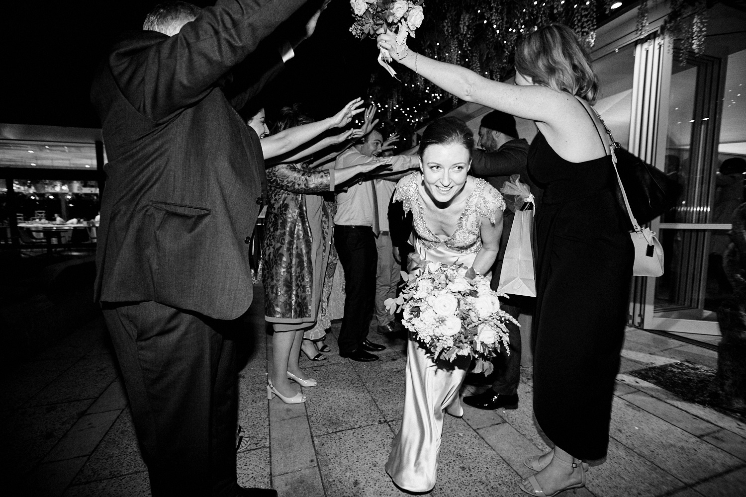 Black and white of bride exiting tunnel at Centennial Homestead wedding