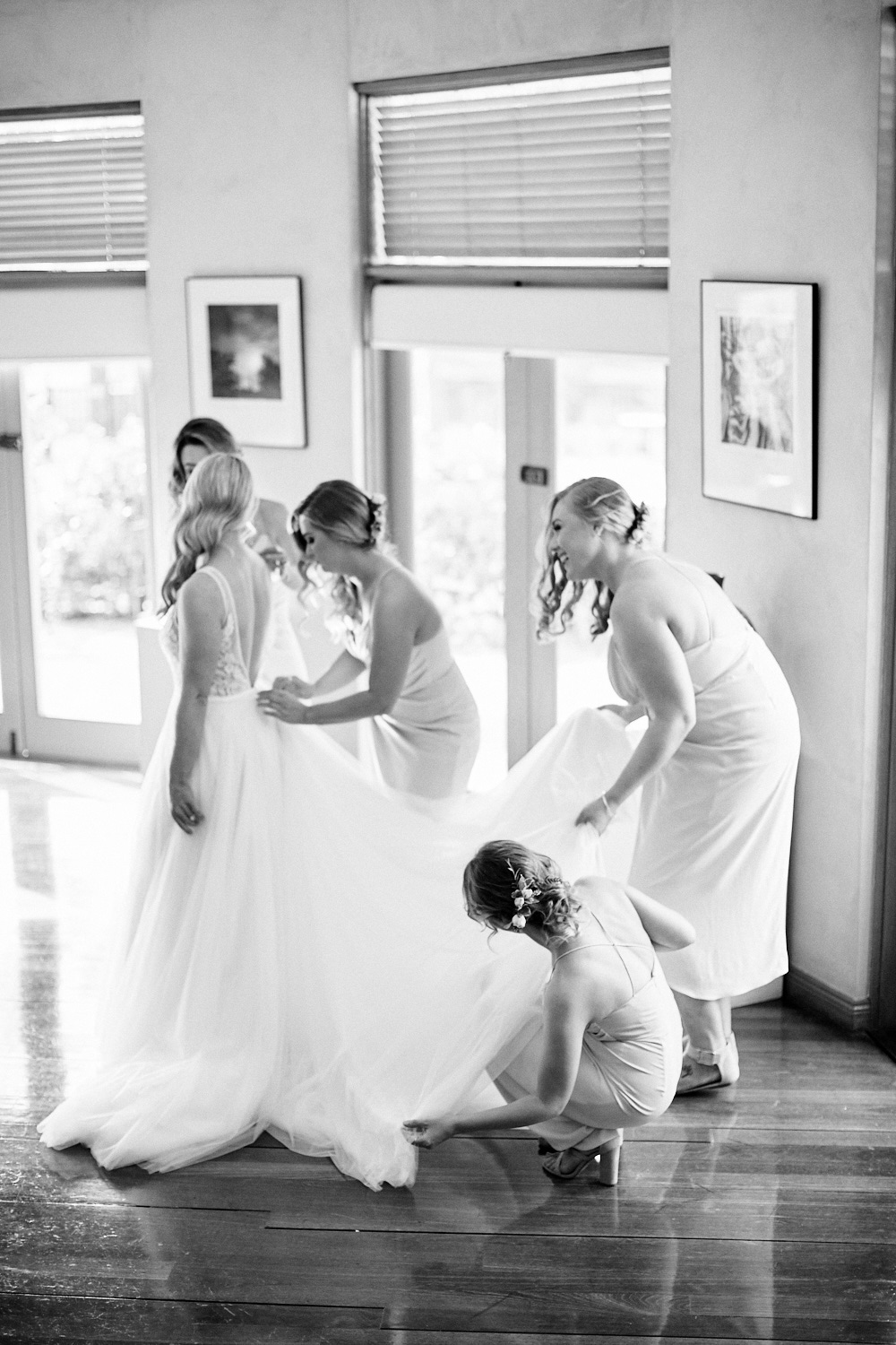 Black and white photo of bridesmaids adjusting brides dress at Estate Tuscany Pokolbin in the Hunter Valley by wedding photographer Joshua Witheford