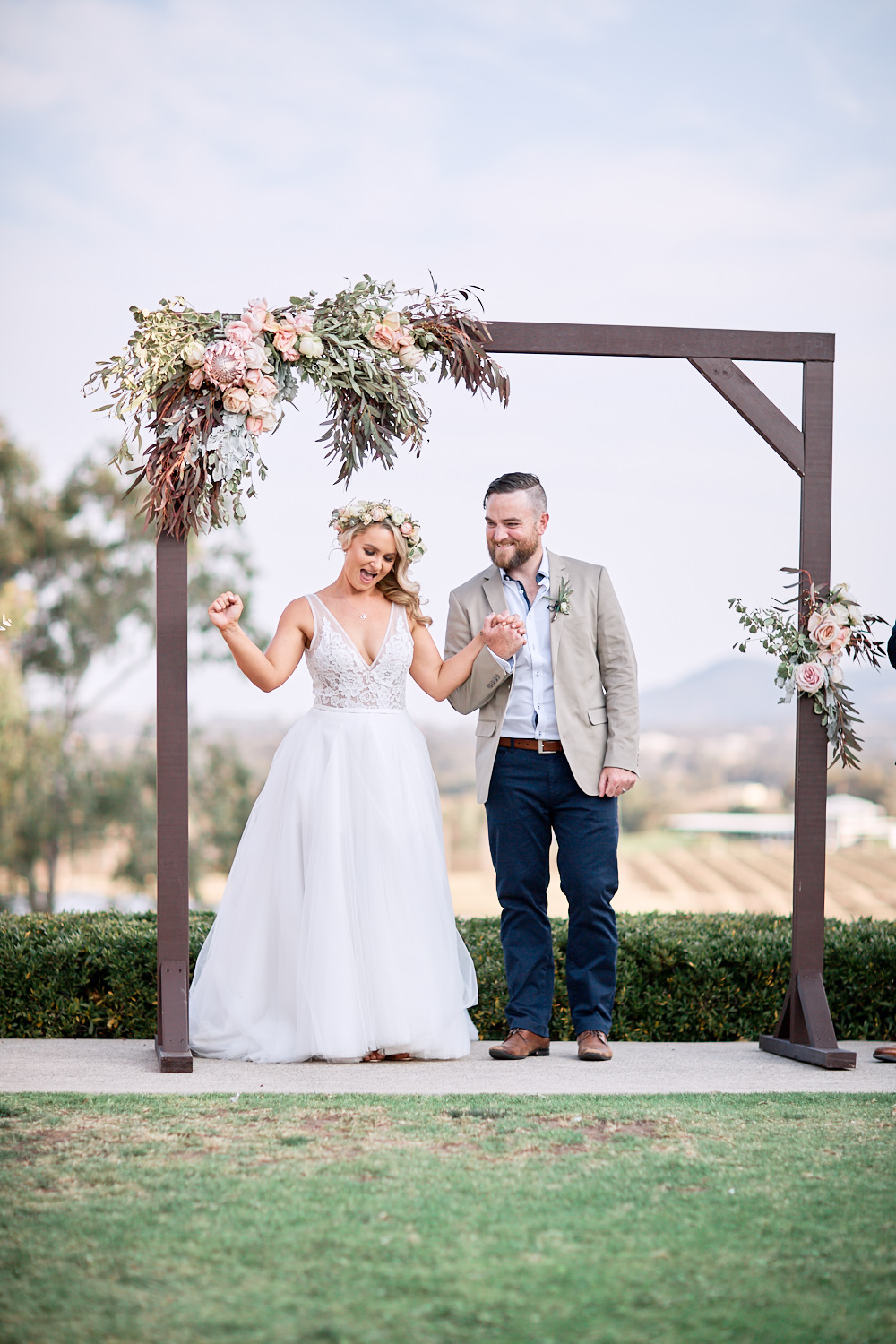 Bride and groom holding hands celebrating under arbor at Estate Tuscany Pokolbin in the Hunter Valley by wedding photographer Joshua Witheford