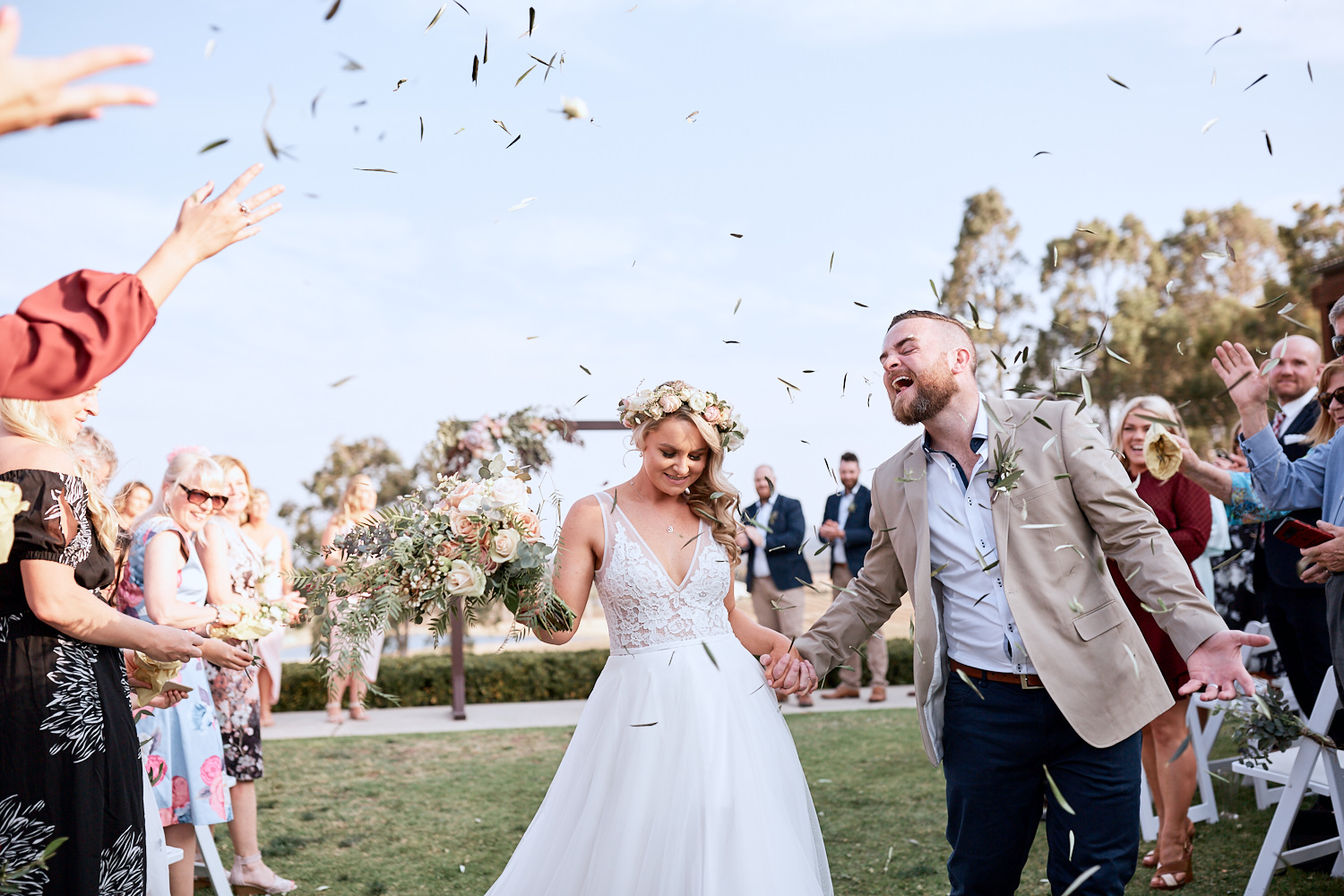 Newlyweds walking down aisle with confetti at Estate Tuscany Pokolbin in the Hunter Valley by wedding photographer Joshua Witheford