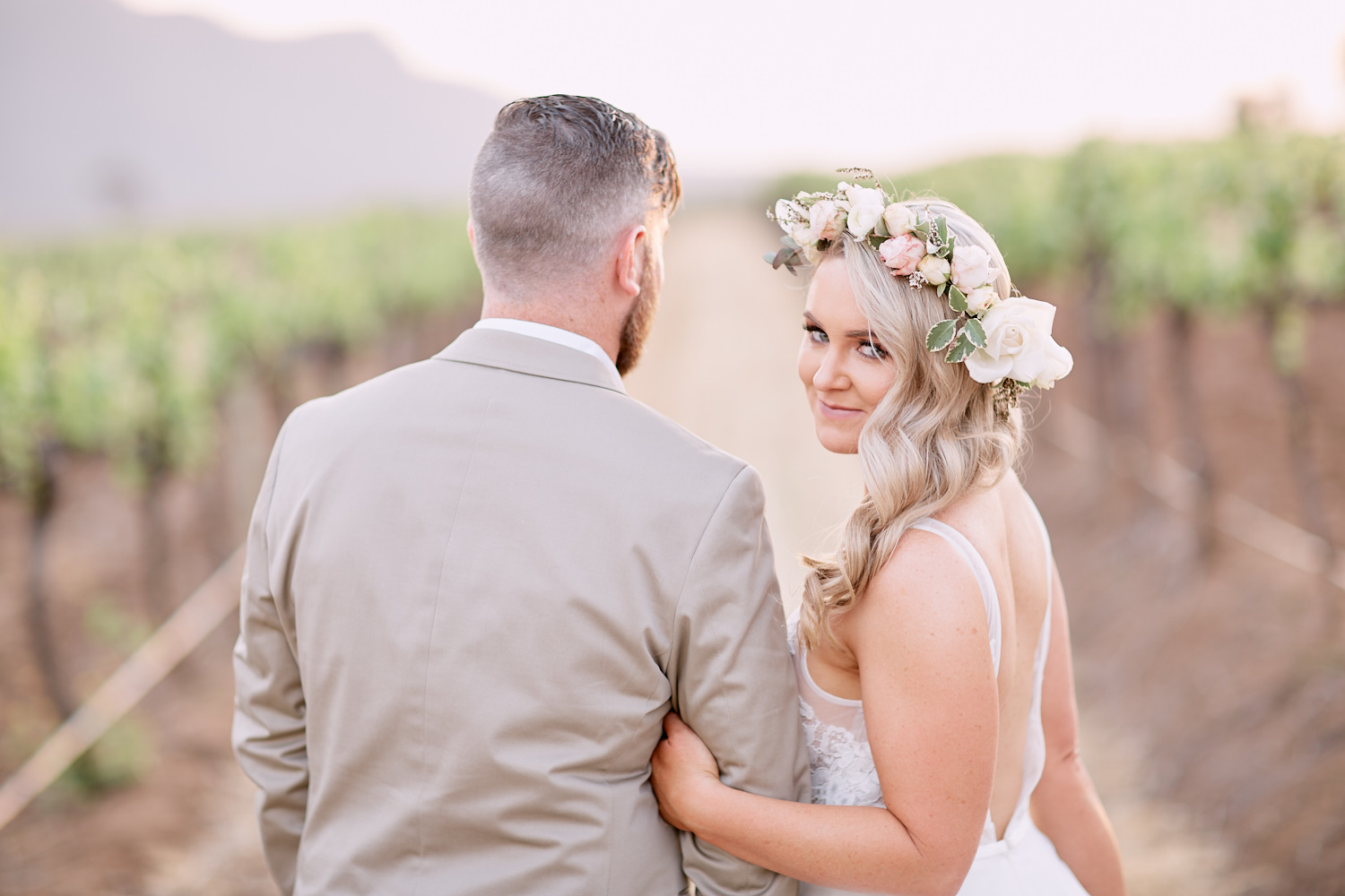 Bride holding grooms arm in vineyard at Estate Tuscany Pokolbin in the Hunter Valley by wedding photographer Joshua Witheford