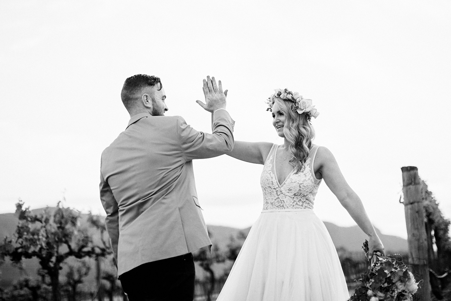 Black and white of bride and groom giving high five in vineyard at Estate Tuscany Pokolbin in the Hunter Valley by wedding photographer Joshua Witheford
