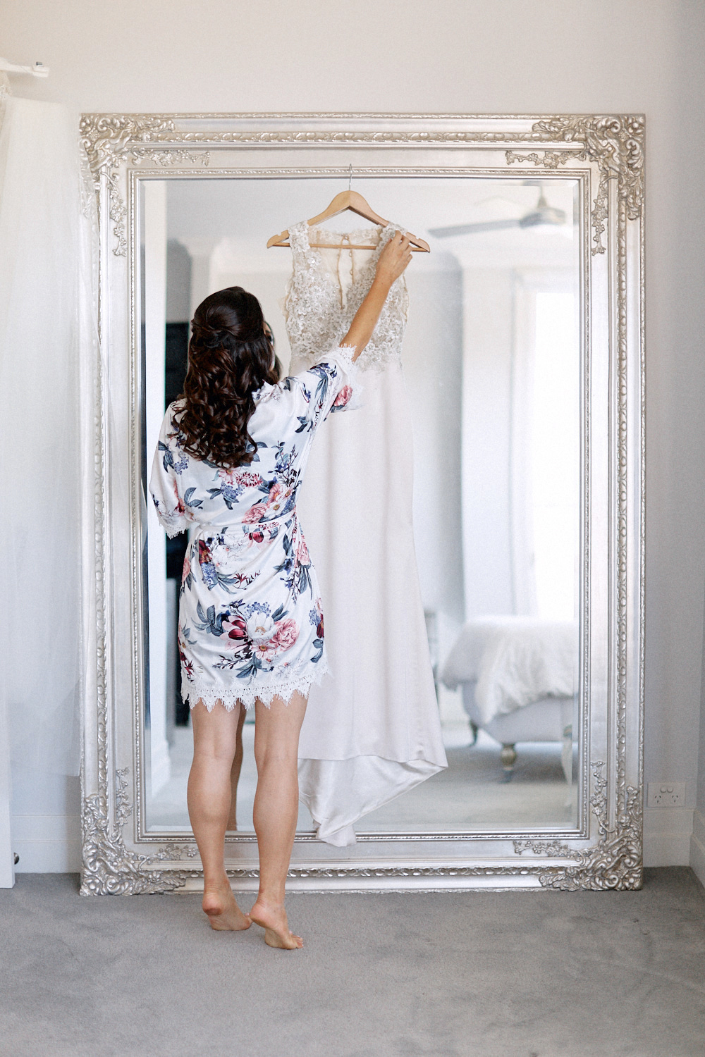 Bride wearing night gown hanging wedding dress on mirror by Blue Mountains wedding photographer Joshua Witheford