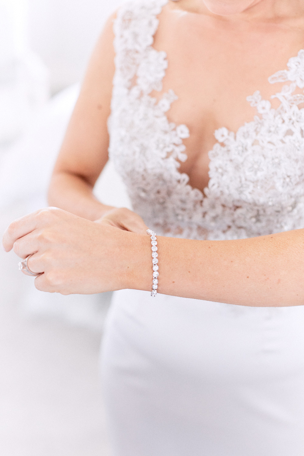 Close up of bride in dress putting on bracelet by Blue Mountains wedding photographer Joshua Witheford