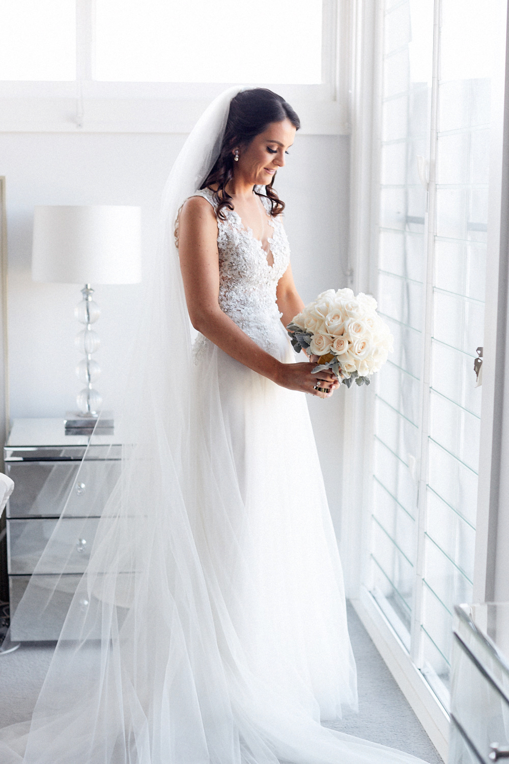 Bride in wedding dress holding and looking at a bouquet of white roses in front of window by Blue Mountains wedding photographer Joshua Witheford