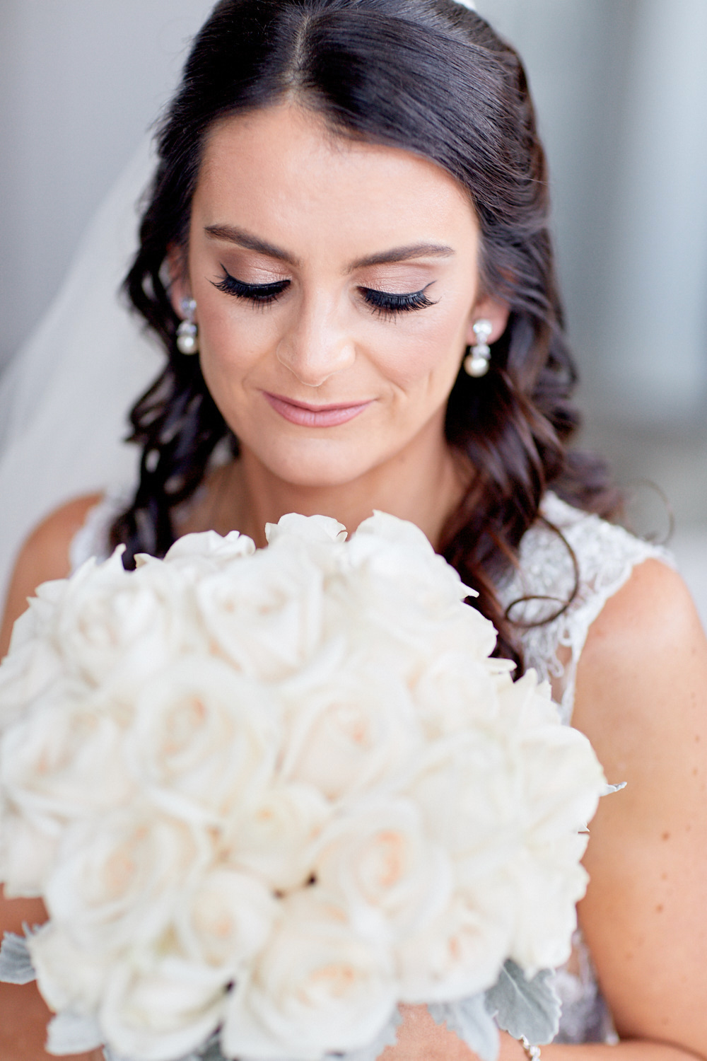 Close up of bride looking at a bouquet of white roses by Blue Mountains wedding photographer Joshua Witheford