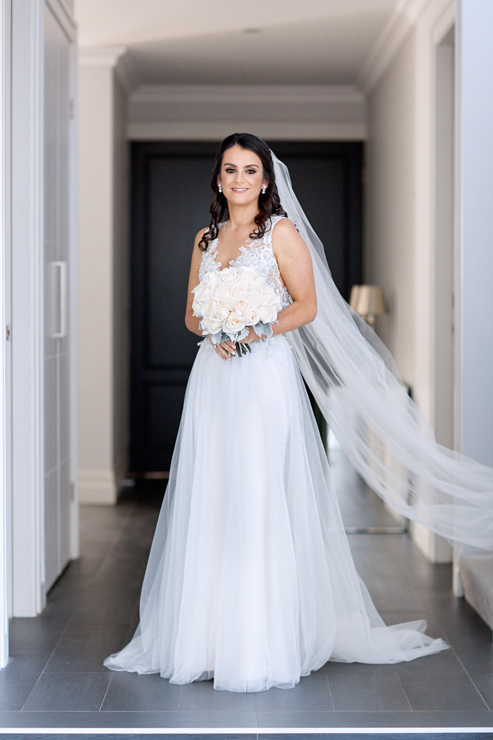 Bride standing in hallway wearing wedding dress and holding a bouquet of white roses by Blue Mountains wedding photographer Joshua Witheford