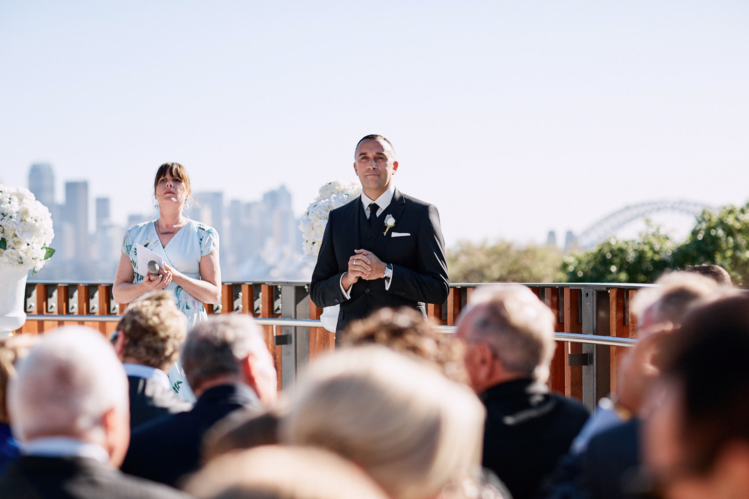 Groom and celebrant standing in front of guests with the Harbour Bridge in the distance on the Centenary Theatre terrace at Taronga Zoo by Blue Mountains wedding photographer Joshua Witheford