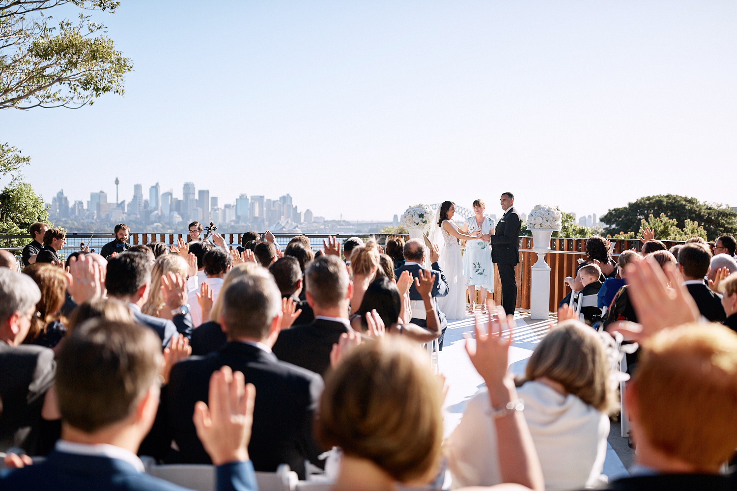 Bride and groom in front of guests with Sydney Harbour in the background on the Centenary Theatre Terrace at Taronga Zoo by Blue Mountains wedding photographer Joshua Witheford