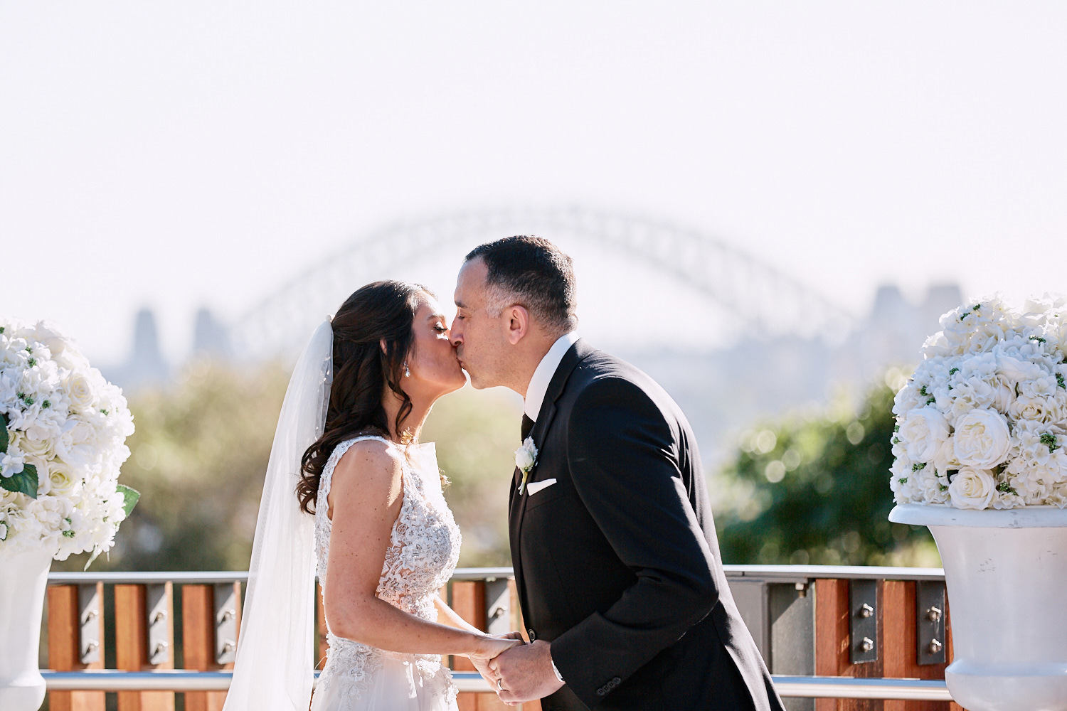 Bride and grooms first kiss in front of the harbour bridge at Taronga Zoo by Blue Mountains wedding photographer Joshua Witheford
