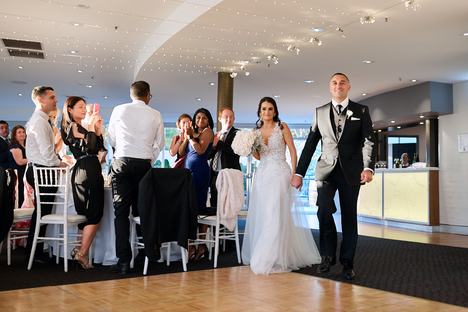 Guests standing and applauding newlyweds entering Taronga Centre reception by Blue Mountains wedding photographer Joshua Witheford