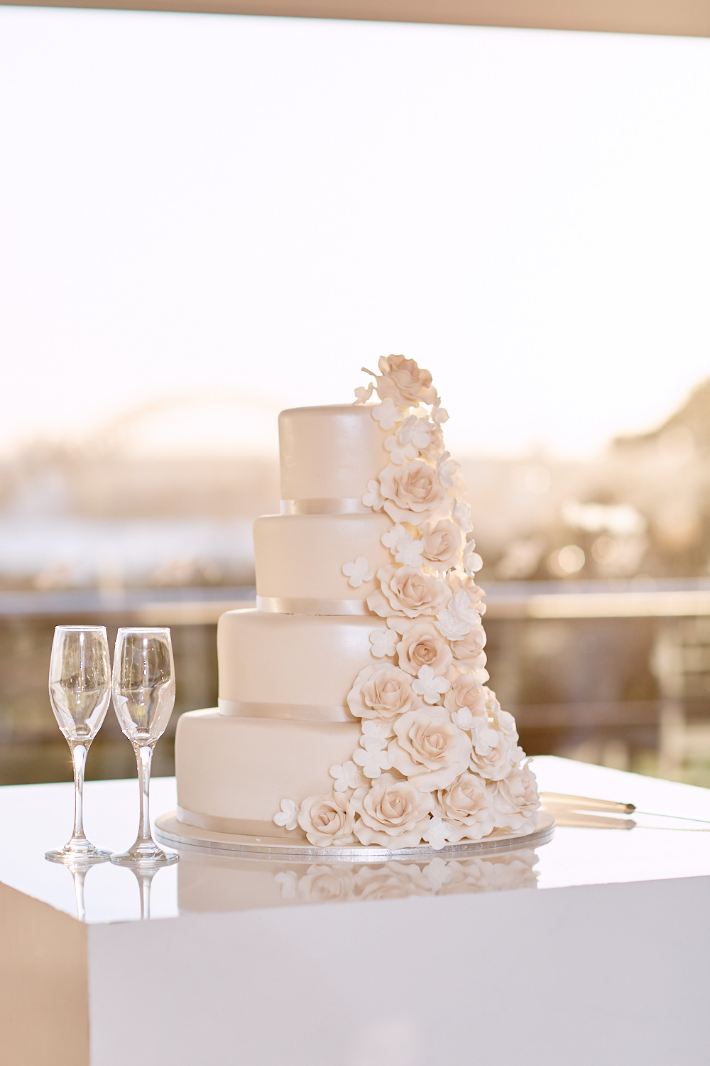 Wedding cake and champagne glasses in front of window in Taronga Centre by Blue Mountains wedding photographer Joshua Witheford