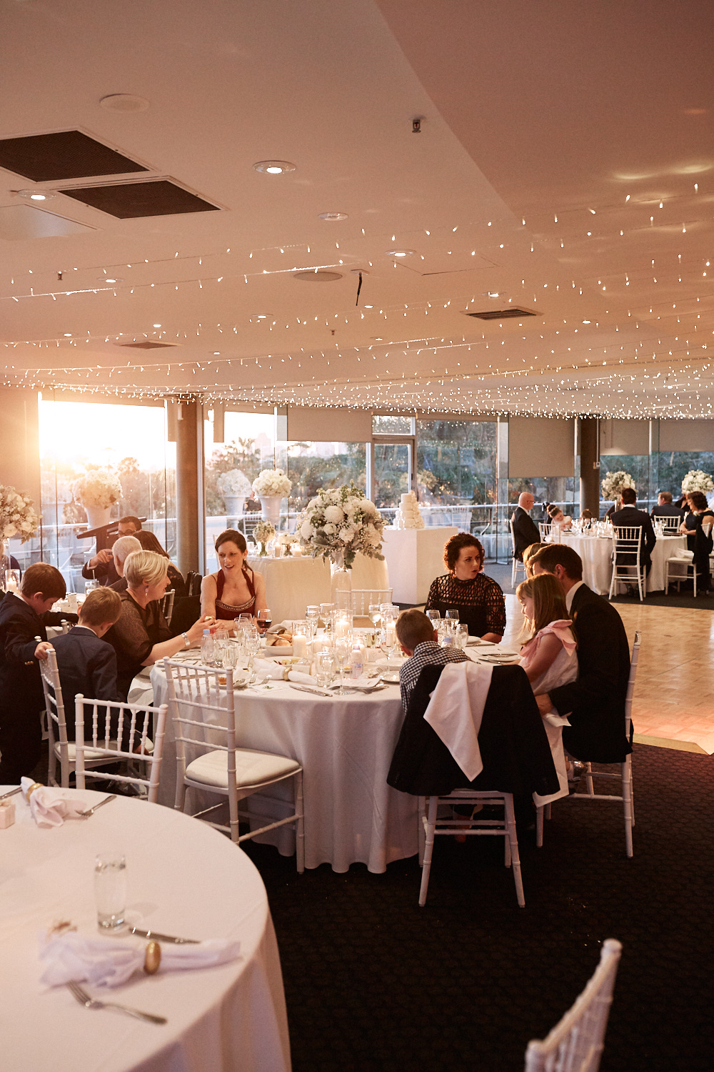 Reception guests sitting at tables in the Taronga Centre by Blue Mountains wedding photographer Joshua Witheford