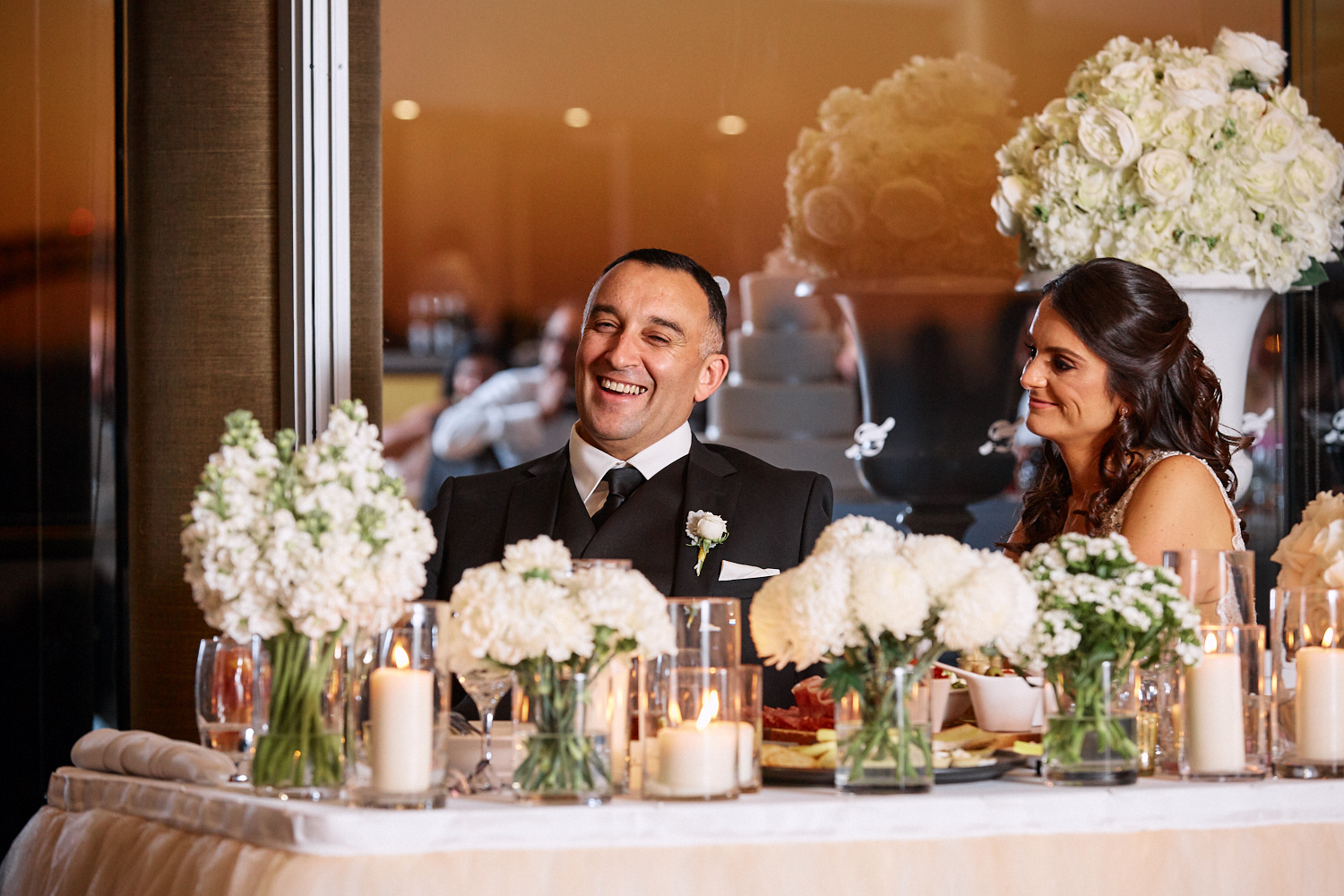 Groom sitting behind table smiling during reception at Taronga Centre by Blue Mountains wedding photographer Joshua Witheford