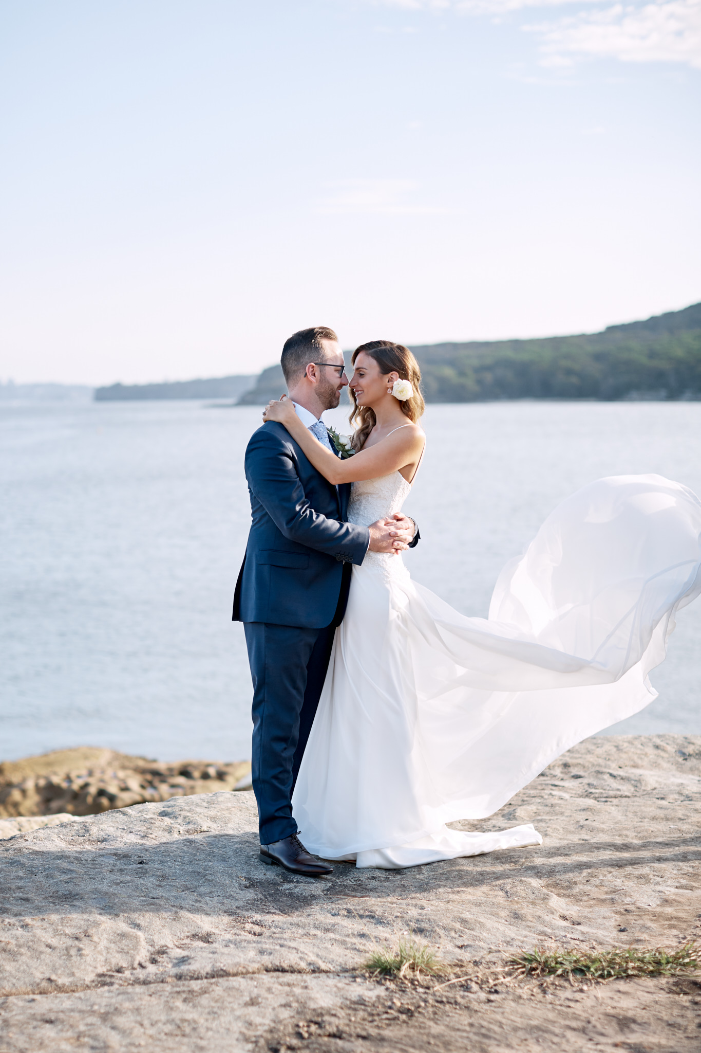Bride and groom on cliff above ocean in manly.jpg