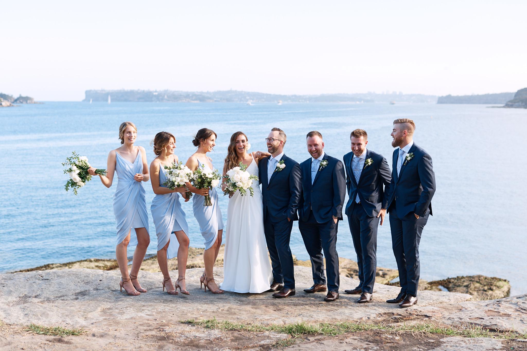 Bridal party laughing by ocean.jpg