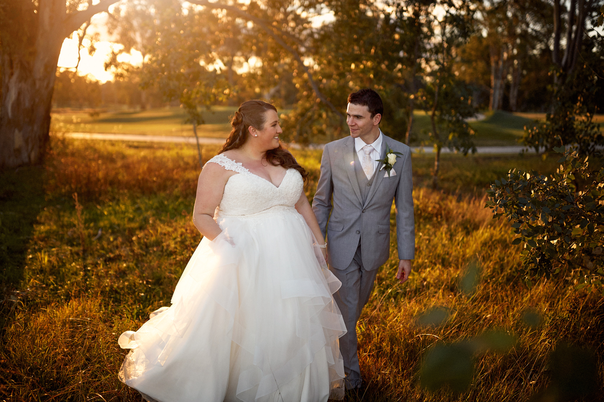 Bride and groom walking through grass at sunset at their lakeside Camden golf club wedding