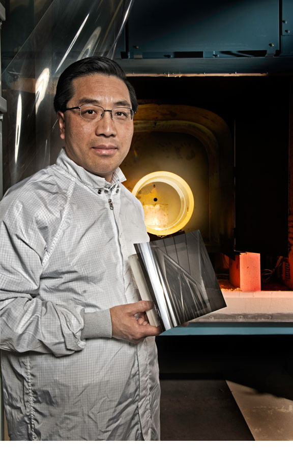 Astrophysicist Will Zhang poses with a curved mirror designed to focus high-energy X Rays.