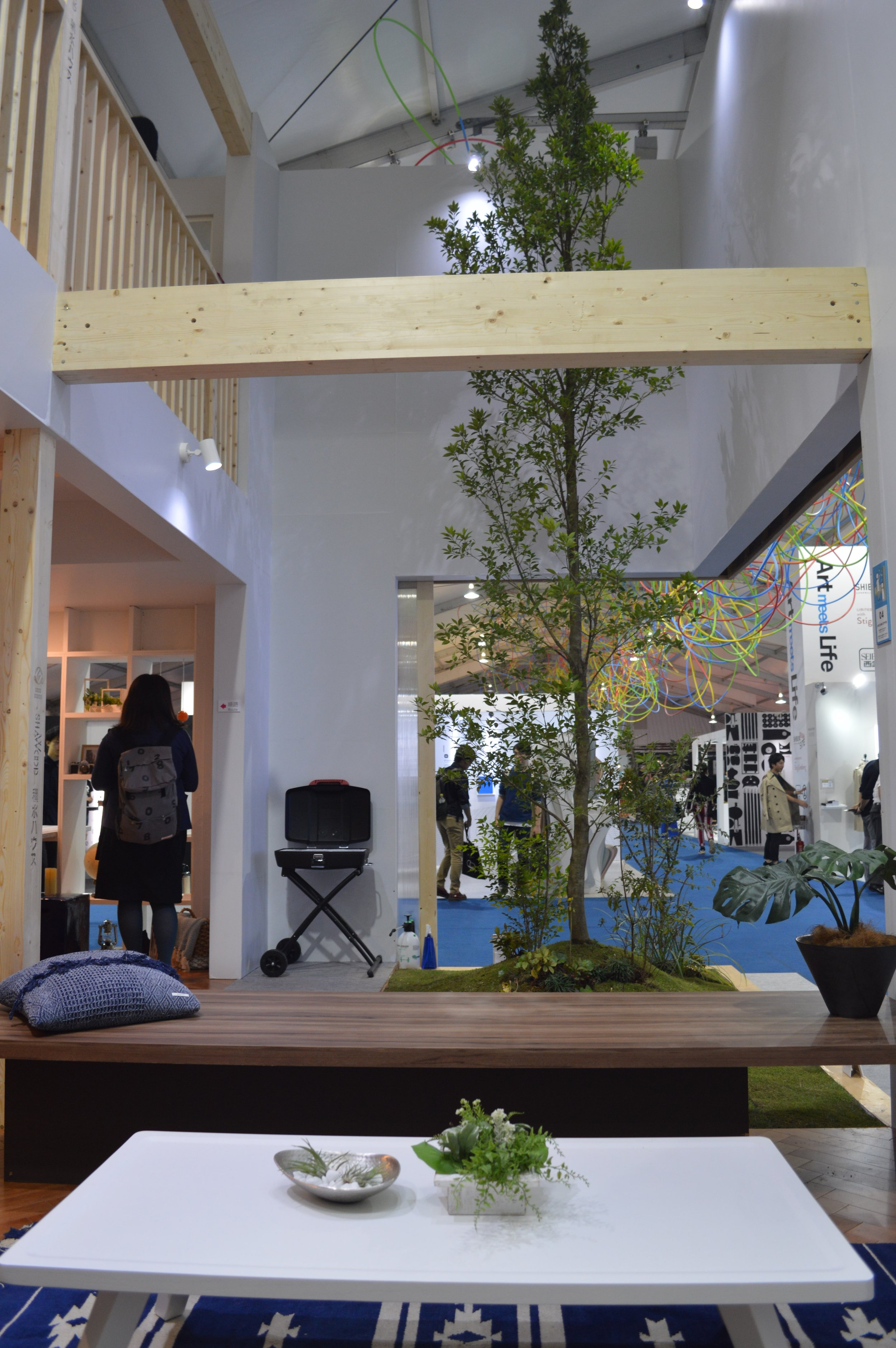 Tokidoki-oide Terrace: A flexible courtyard with a sculptural tree. It becomes a private space by closing the outer doors or an open space by leaving the doors open. This is the view from the swinging sofa in the living room.