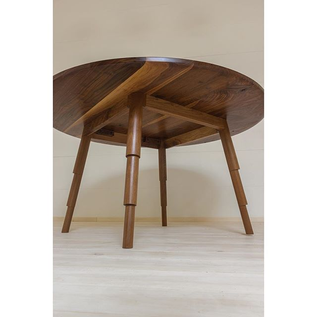 """""""Time of Grace"""" round table. Fun shot of the underside and leg design. Turned from a single solid piece of wood, each leg is hand turned giving it a unique look. Shown in Walnut."""
