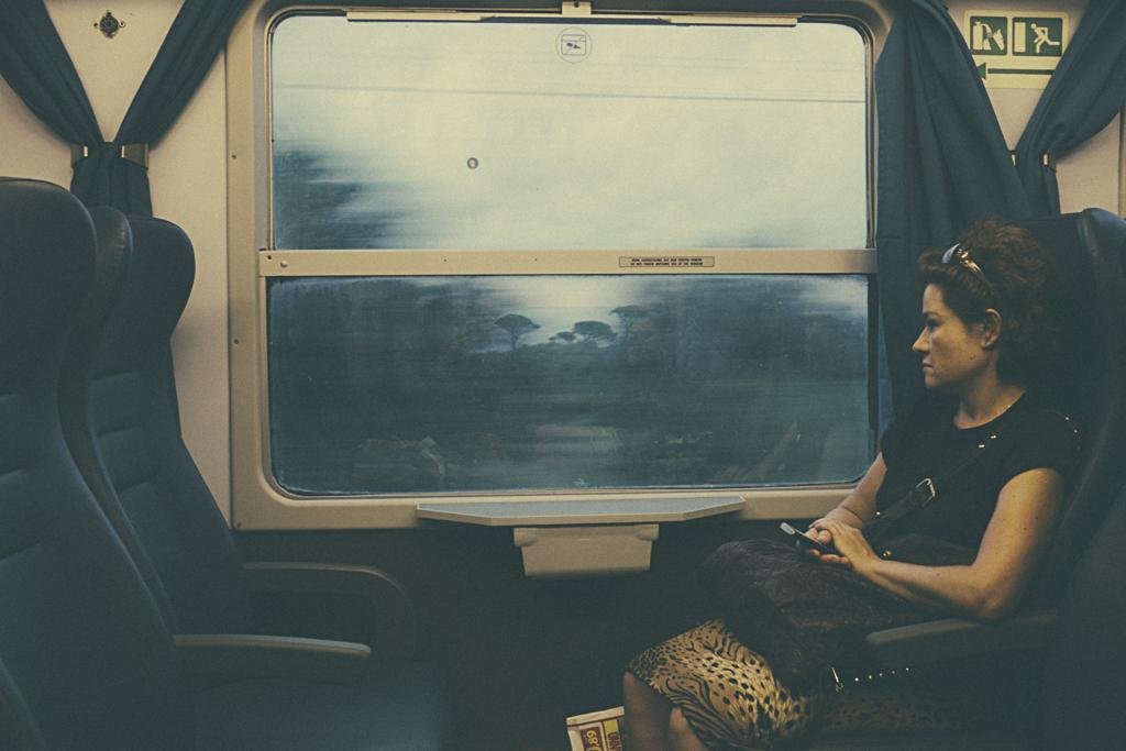 Fotografía mujer viajando en tren de Cefalu a Palermo. Caravanbook photobooks. Travel blog.