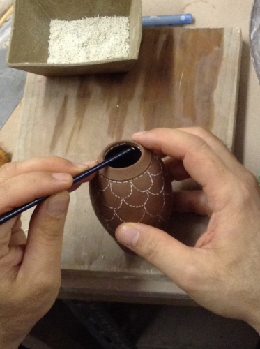 Applying stitches to wet vase with end of paintbrush