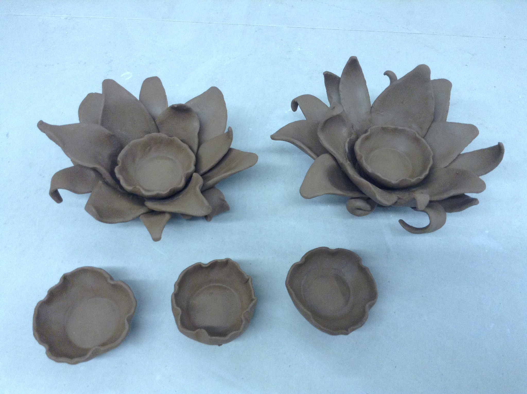 Two flower forms, shown with three separate candle-holding cups.