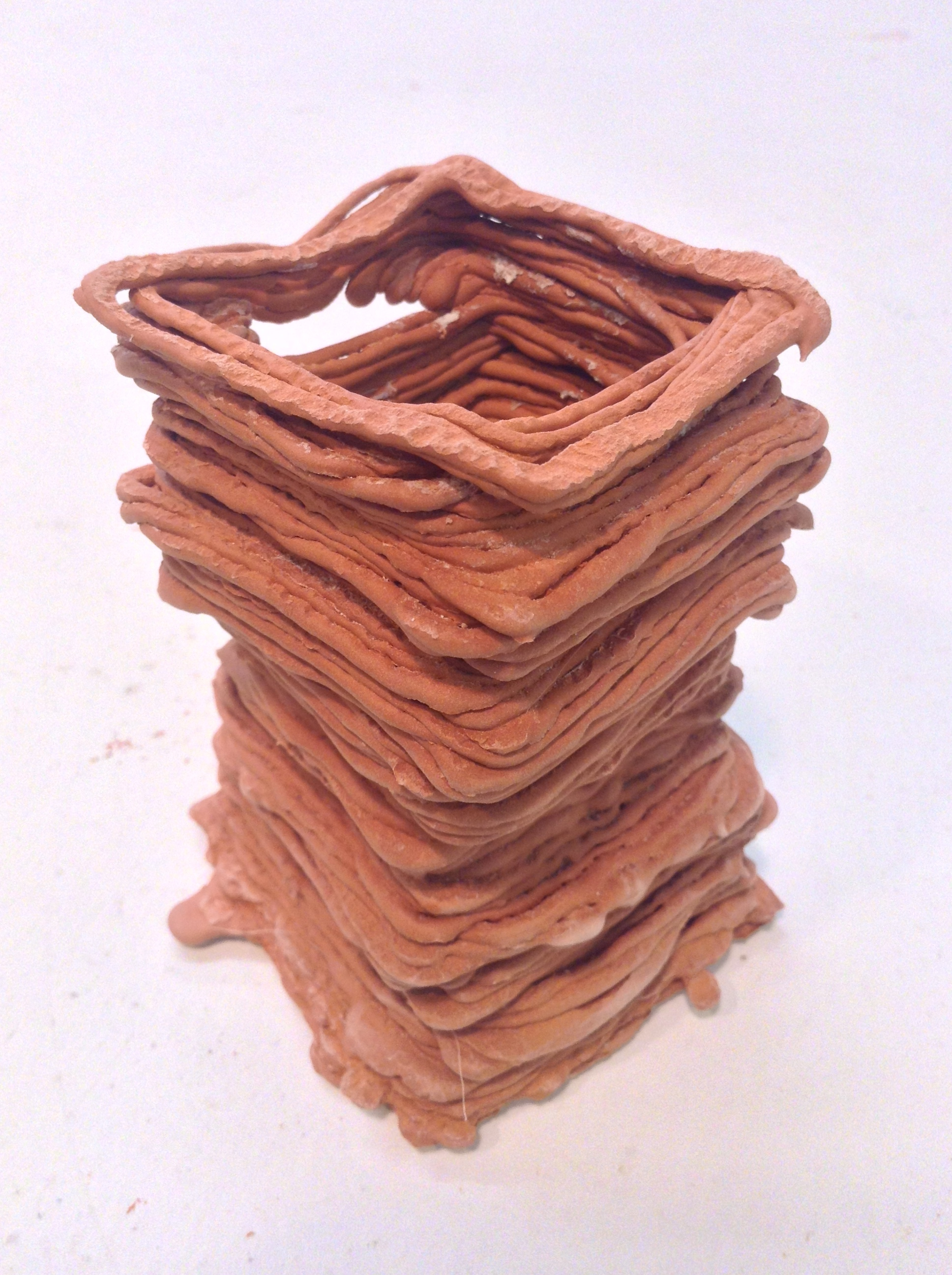 A tall stack of slip-trailed layers. Low-fire clay, cone 05 oxidation, unglazed.